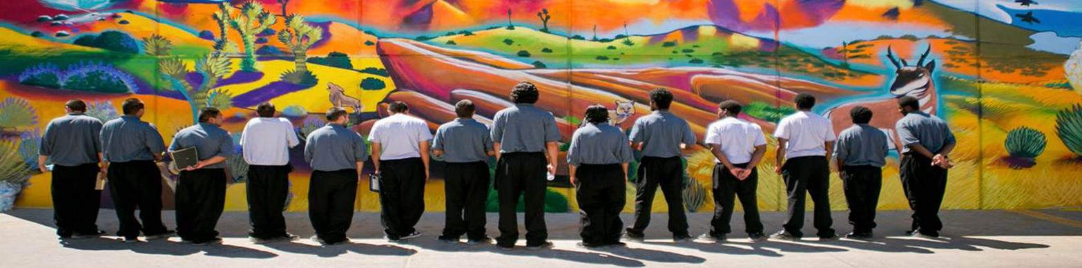 image of young men from behind facing a mural